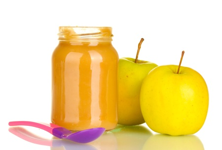 Jar with apple baby food and spoon isolated on white photo