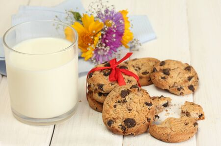 glass of milk, chocolate chips cookies with red ribbon and wildflowers on wooden table photo