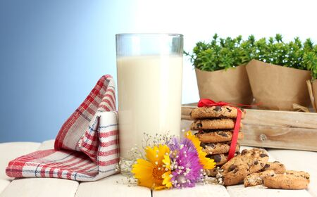 glass of milk, chocolate chips cookies with red ribbon and wildflowers on wooden table on blue background Stock Photo - 14071392