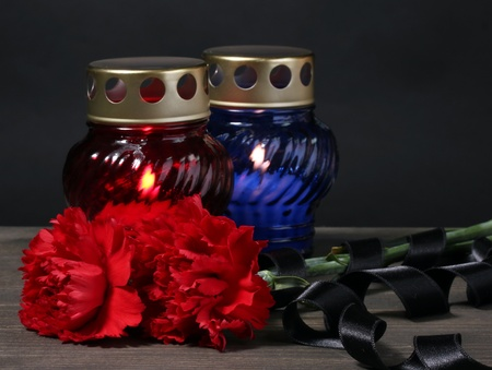Memory lantern with candles, red carnations and ribbon on wooden table on grey background photo