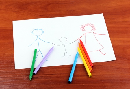 Childrens drawing of family and pencils on wooden background photo