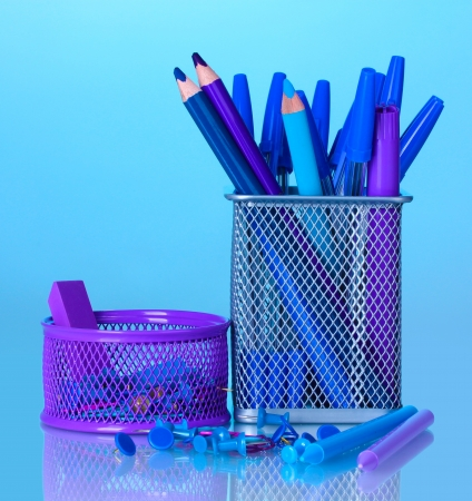 Color holders for office supplies with them on bright colorful background photo