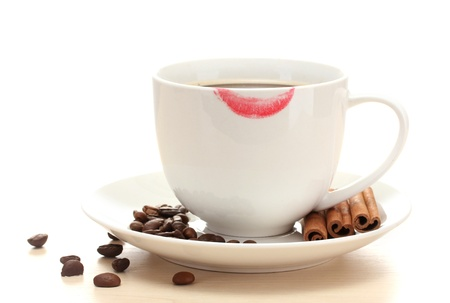cup of coffee with lipstick mark beans and cinnamon sticks isolated on white photo