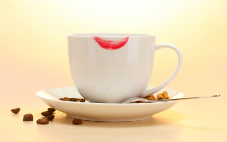 cup of coffee with lipstick mark beans and cinnamon sticks on wooden table Stock Photo - 14069579