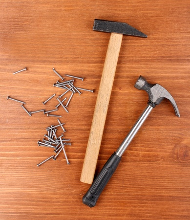 Hammers and metal nails on wooden background photo