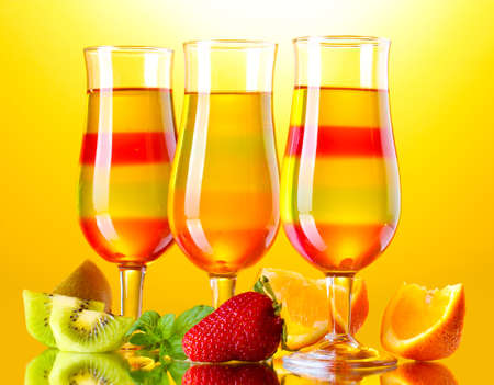 fruit jelly in glasses and fruits on yellow background photo