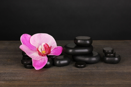 Spa stones with orchid flower on wooden table on grey background photo