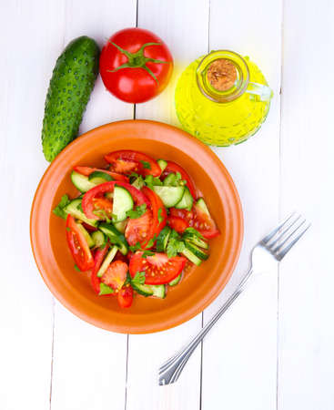 Fresh salad with tomatoes and cucumbers on white wooden background photo