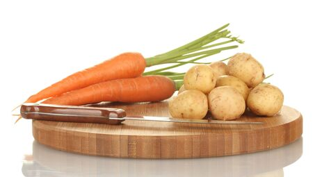 young potatoes and carrots on a cutting board with knife isolated on white Stock Photo - 14077453