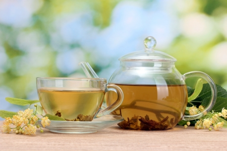 teapot and cup with linden tea and flowers on wooden table in garden Stock Photo - 14076717