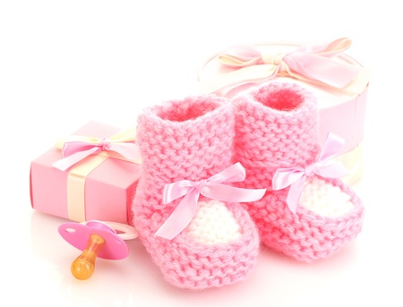 shoe box: pink baby boots, pacifier, gifts and flower isolated on white