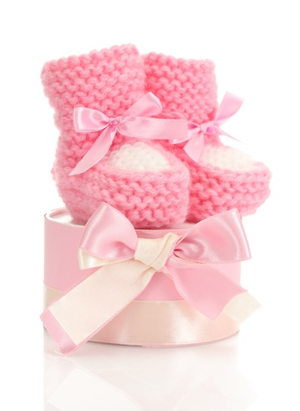 pink baby boots and gift isolated on white photo