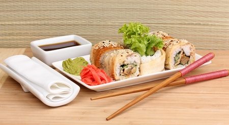 Tasty rolls served on white plate with chopsticks on wooden table on light background Stock Photo - 14077969