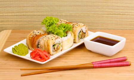 Tasty rolls served on white plate with chopsticks on wooden table on light background Stock Photo - 14077988