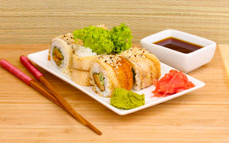 Tasty rolls served on white plate with chopsticks on wooden table on light background Stock Photo - 14078009