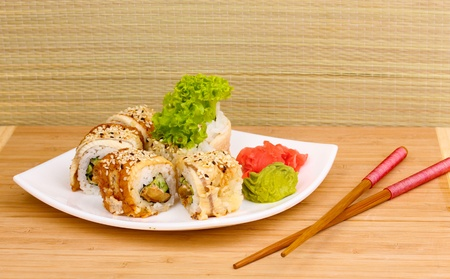 Tasty rolls served on white plate with chopsticks on wooden table on light background Stock Photo - 14078021