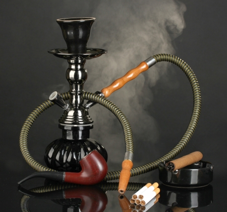 Smoking tools - a hookah, cigar, cigarette and pipe on black background photo