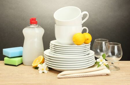 empty clean plates, glasses and cups with dishwashing liquid, sponges and lemon on wooden table on grey background Stock Photo - 14077998