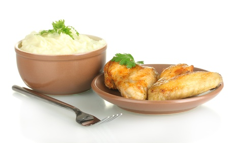 Mashed potato with parsley in the bowl and roasted chicken wings in the plate isolated on white photo