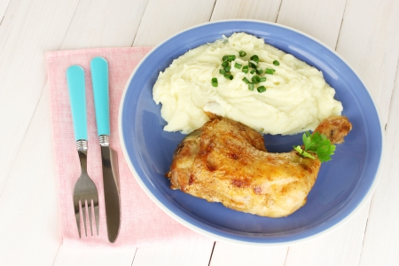 roasted chicken leg with mashed potato in the plate on white wooden table close-up photo