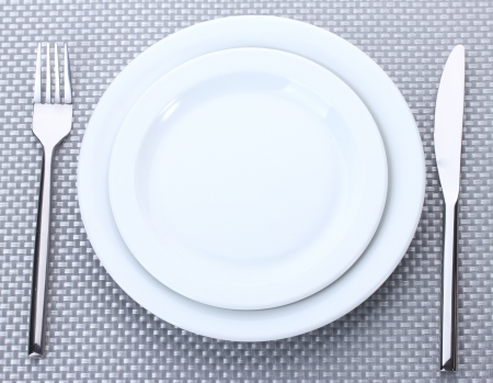 White empty plates with fork and knife on a grey tablecloth