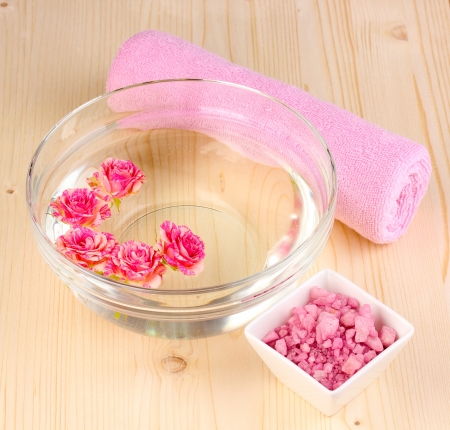 Bowl with roses, spa setting on wooden background photo