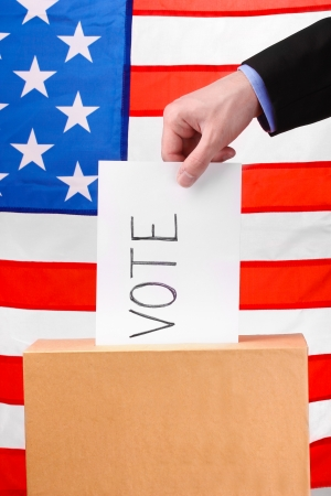 political system: Hand with voting ballot and box on Flag of USA