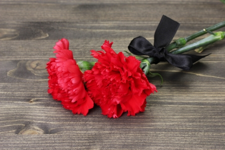 carnations and black ribbon on grey wooden background photo