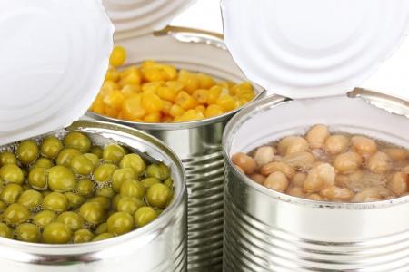 tin cans: Open blikjes van maïs, bonen en erwten op wit wordt geïsoleerd Stockfoto
