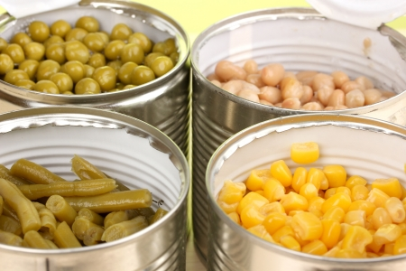 canned food: Open tin cans of peas, corn, bean and french bean close-up