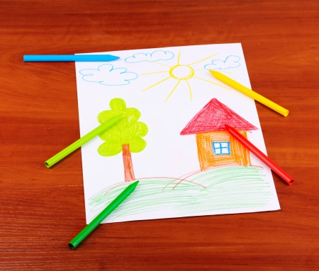 Childrens drawing of house and pencils on wooden background photo