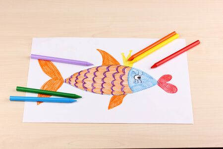 Children's drawing of golden fish and pencils on wooden background Stock Photo - 14078000