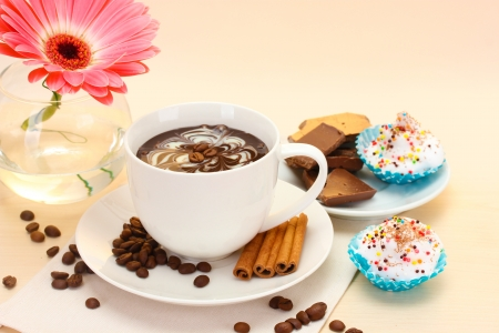 cup of coffee and gerbera, beans, cinnamon sticks on wooden table photo