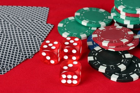 poker chips, dice and cards on a red table photo