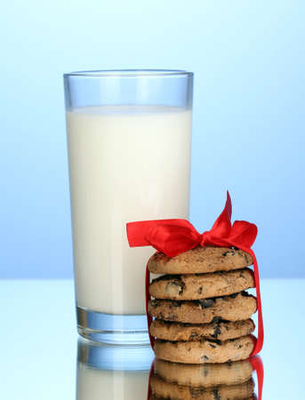 Glass of milk and cookies on blue background photo