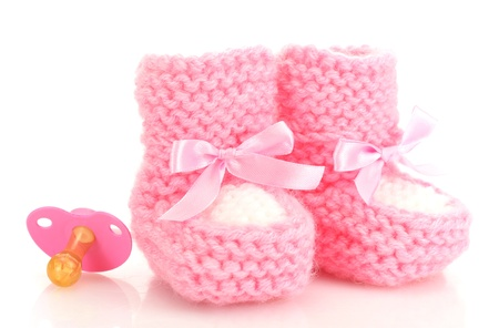 pink baby boots and pacifier isolated on white photo
