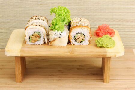 Tasty rolls served on wooden plate on wooden background photo