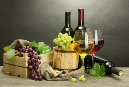 barrel, bottles and glasses of wine and ripe grapes on wooden table on grey background Stock Photo - 14092211