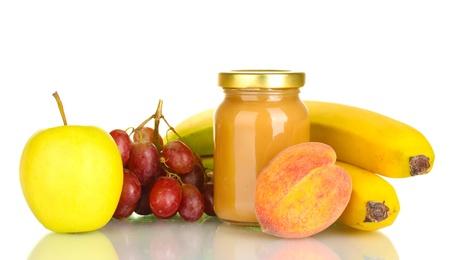Jar met fruit babyvoeding en fruit op wit wordt geïsoleerd Stockfoto