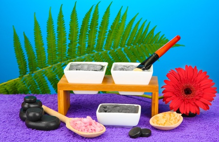 cosmetic clay for spa treatments on bright blue background close-up photo