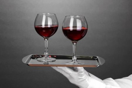 Hand in glove holding silver tray with wineglasses on grey background photo