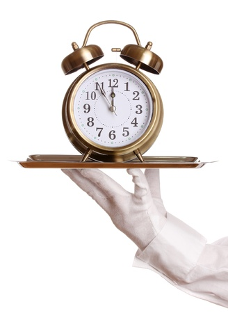 Hand in glove holding silver tray with alarm clock isolated on white photo