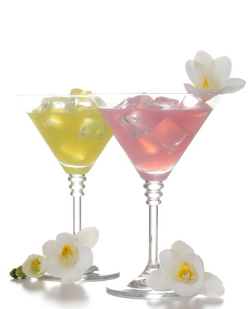 martini glasses of cocktails with ice and flowers isolated on white photo