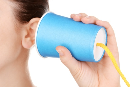 Human ear and paper cup near it close-up isolated on white photo