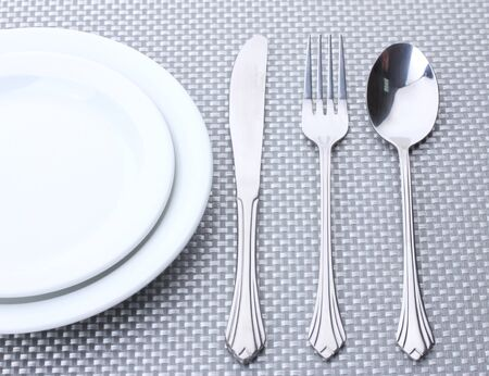fork knife spoon: White empty plates with fork, spoon and knife on a grey tablecloth