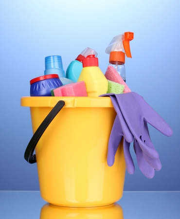 cleaning supplies: Bucket with cleaning items on blue background