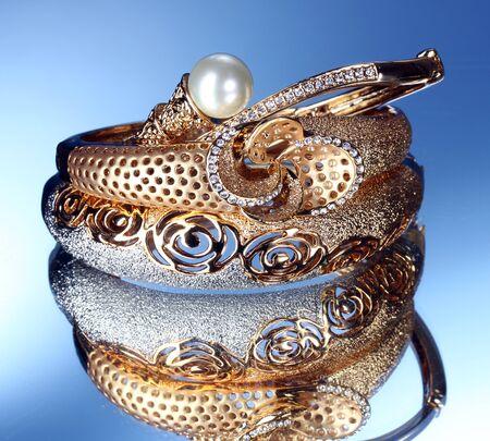 Beautiful gold bracelets on blue background photo