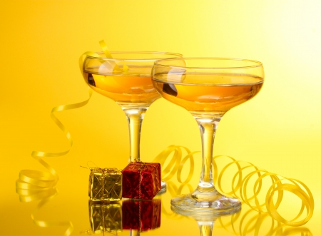 glasses of champagne, gifts and streamer on yellow background photo