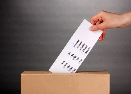 Hand with voting ballot and box on grey background Stock Photo - 14099248