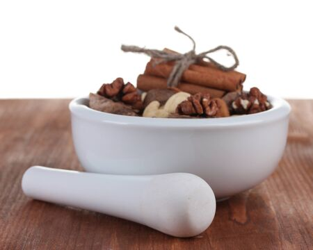 Composition of mortar with nuts and cinnamon on wooden photo